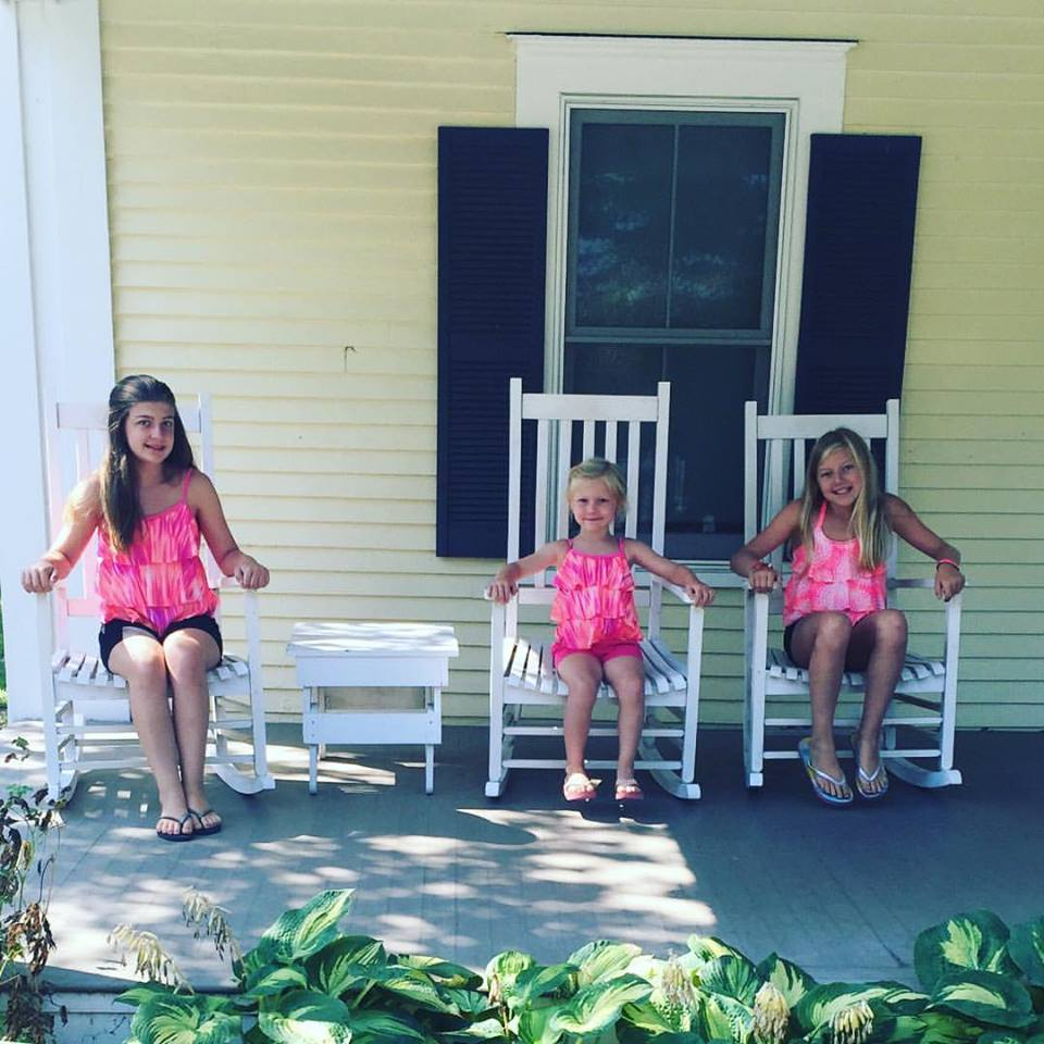Three girls sitting on the porch